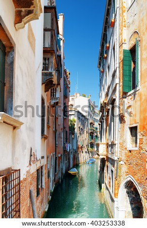 View of the Rio de Santa Maria Formosa Canal from the Ponte de Ruga Giuffa in Venice, Italy. Boats parked beside old medieval houses on canal of Venice. Venice is a popular tourist destination. - stock photo