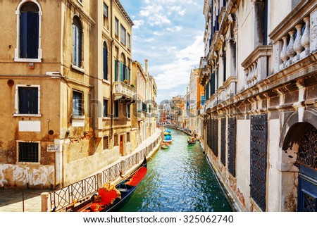 View of the Rio Marin Canal with gondolas and boats from the Ponte de la Bergami in Venice, Italy. Venice is a popular tourist destination of Europe. - stock photo