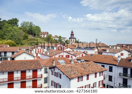 View of the rooftops of typical buildings and belfry of Saint-Vicent church of Ciboure in Basque country. Aquitaine, France. - stock photo