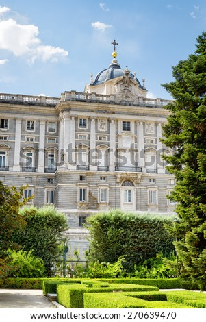 View of the Royal Palace of Madrid from garden on the blue sky background in Spain at summer time. Madrid is a popular tourist destination of Europe.