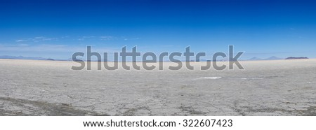View of the Salar of Uyuni against a blue sky during the dry season, the salt plains are a completely flat expanse of dry salt. Bolivia