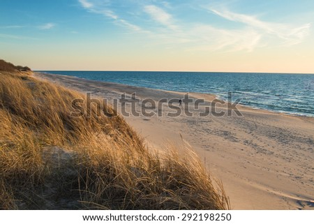 View of the sandy beach and the Baltic Sea at sunset - stock photo