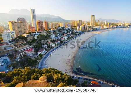 View of the sea coast with people bathing in the blue sea, on a background of city at sunset (Spain, Benidorm - Fish Eye Lens) - stock photo
