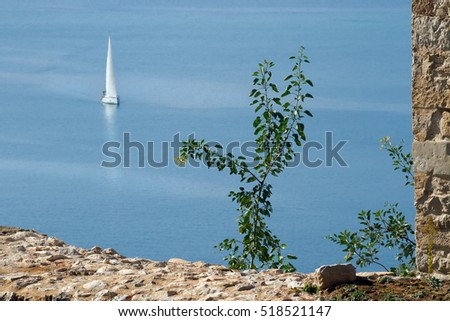 View of the sea with a floating sailing vessel from a high fortification. Nafplion (Nafplio), Grecee