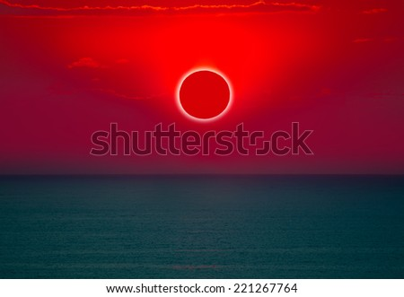 View of the sea with the full solar eclipse at sunset - stock photo