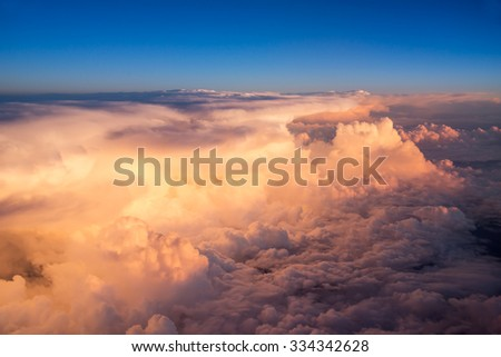 View of the sky and clouds from the airplane porthole at sunset - stock photo