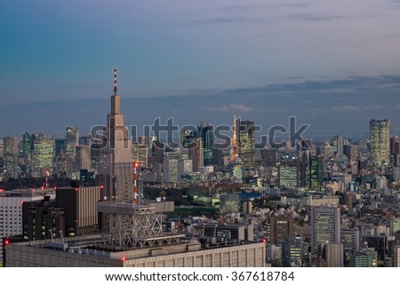 view of the skyscrapers in Tokyo, Japan in the evening time with Tokyo Tower the symbol of Japan and blue layer of sky - stock photo