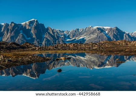 View of the snow-capped mountains reflected on the water, Greenland. - stock photo
