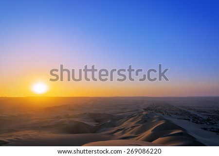 View of the sun setting over sand dunes in Huacachina, Peru - stock photo