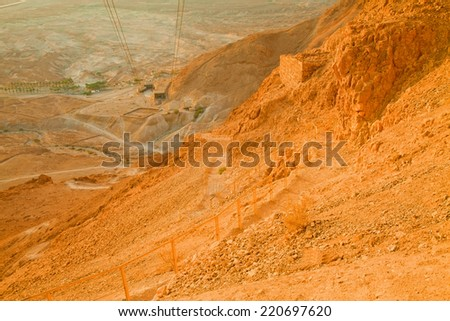 View of the the valley laying under the Snake Path ascend to Massada Fortress (Israel) at dawn (unusual desert sunrise lighting) - stock photo