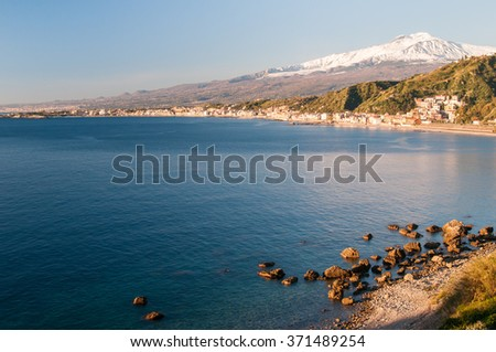 View of the touristic village Giardini Naxos, East sicily, in the early morning with a view of Mount Etna - stock photo