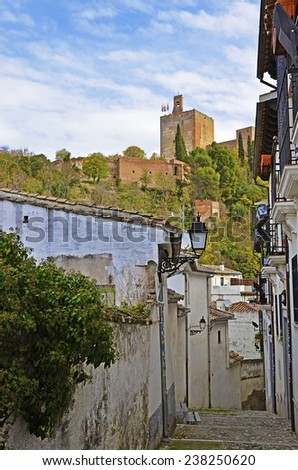 view of the Tower of the lamp of the Alhambra from a narrow street in Granada - stock photo