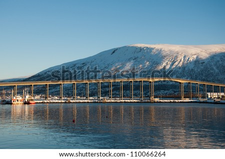 View of the Tromsoe's bridge from the middle of the fjord - stock photo