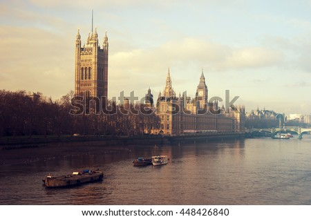 View of the UK Houses of Parliament - the Palace of Westminster - in London, England, from across the Thames in the evening. Added vintage filter. - stock photo