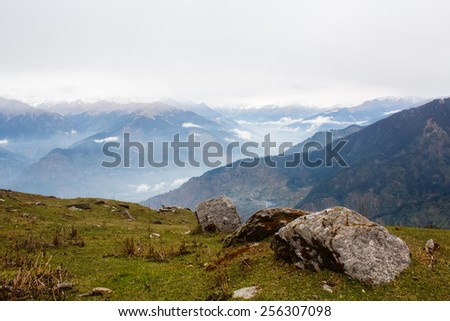 view of the valley in himalayan mountains covered with clouds - stock photo