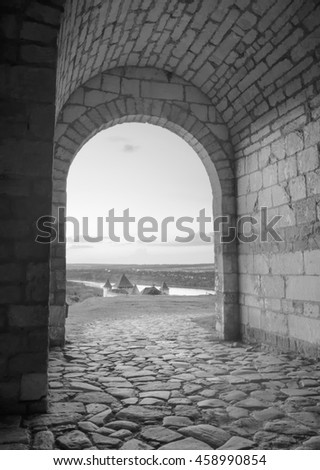 View of the valley with medieval castle from the arch in a stone wall.