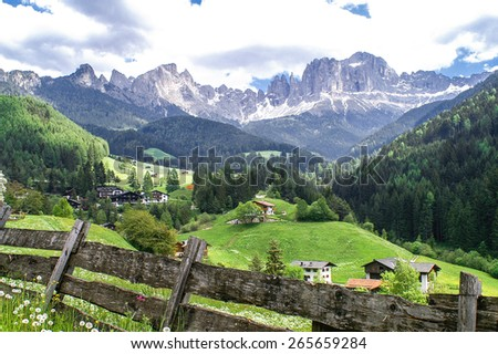 View of the village Tiers and the Rosengarten mountains in the Dolomites, South Tyrol - stock photo
