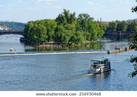View of the Vltava river and Strelecky island with cruise tour boats from the Charles Bridge. The Charles Bridge is a famous historic bridge that crosses the Vltava river in Prague, Czech Republic. - stock photo