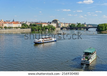 View of the Vltava river with cruise tour boats from the Charles Bridge. The National Theatre and the Legion bridge are seen. Prague, Czech Republic. - stock photo