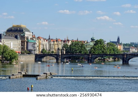 View of the Vltava river with many leisure pedal boats from the Charles Bridge. The National theatre and the Legion bridge are seen. Prague, Czech Republic. - stock photo