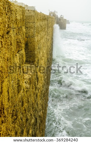 View of the Western Sea Wall of the old city of Acre in a stormy winter day. Israel - stock photo
