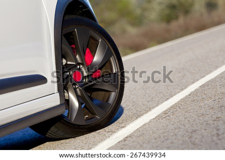 View of the wheel of a withe sport car on a road.  Wheel on a road.  - stock photo