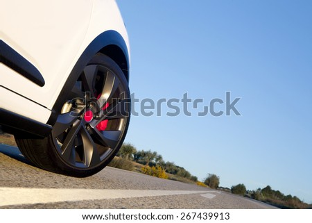 View of the wheel of a withe sport car on a road with blue sky on the background.  Wheel on a road