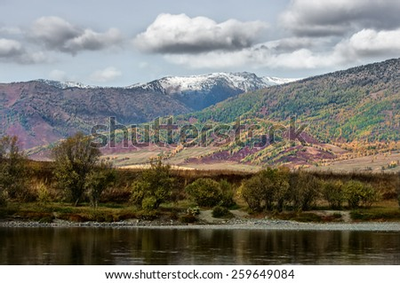 View of the wooded colored mountains and river in the fall - stock photo