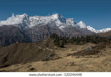 View of the yellow helicopter the peak Nupla (5885 m), Kongde (6186 m), and Nup (6035 m) in the background - Nepal, Himalayas - stock photo