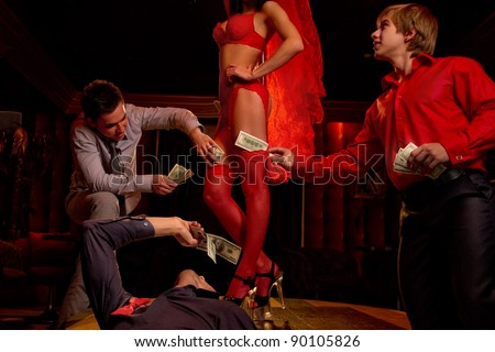 View of three men offering money to a stripper on stage - stock photo