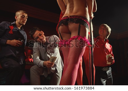 View of three men offering money to strippers on stage - stock photo