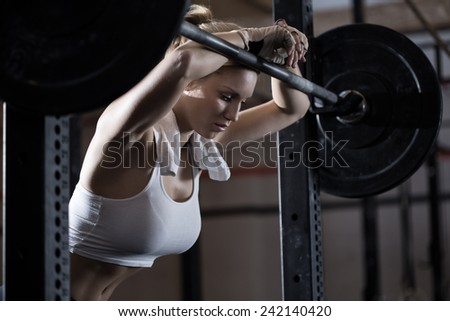 View of tired girl after weight lifting - stock photo