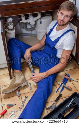 View of tired man during sink repair