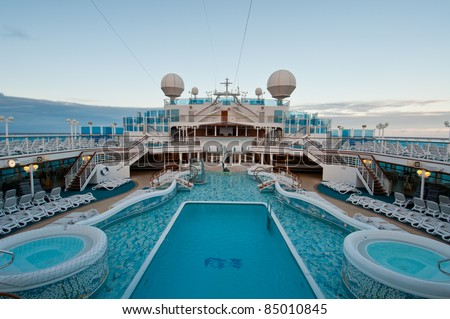 View of top deck of cruise ship with luxurious pools and spa facilities. - stock photo