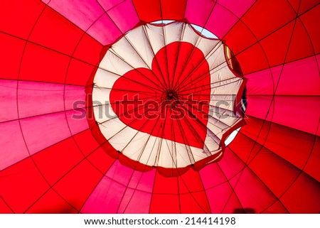 View of top of heart hot air balloon during inflation - stock photo