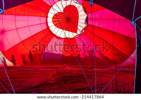 View of top of heart hot air balloon during inflation with silhouettes of people - stock photo