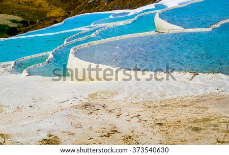 View of travertine pools and terraces. Nature landmarks in Turkey - landscape with travertines and turquoise water. Thermal springs and terrace in turkish resort Pamukkale.
