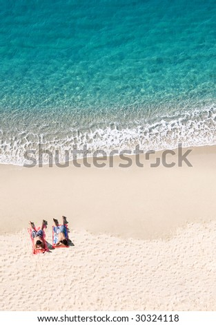 View of two people lying on tropical beach, lots of copyspace - stock photo