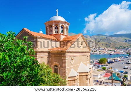 View of typical Greek church with red roof with city port in background, southern Greece  - stock photo