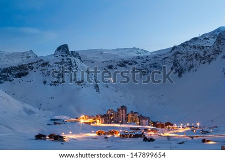 View of Val Claret from Tignes Le Lac at night. Light trails can be seen from traffic passing through Val Claret, and also from machines on the mountain grooming pistes. - stock photo