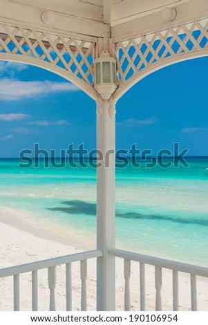 View of Varadero beach in Cuba framed by the columns of a beautiful wooden terrace - stock photo