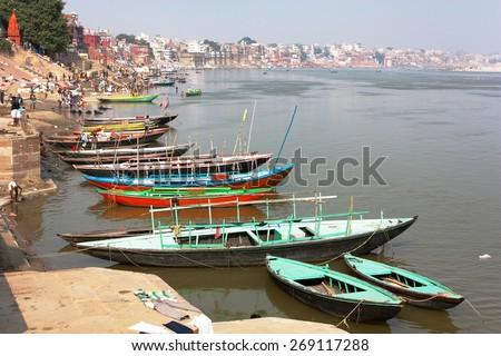 View of Varanasi with boats on sacred Ganga River - Uttar Pradesh - India - stock photo