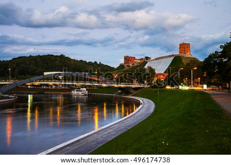 View of Vilnius, Lithuania in the evening. Cloudy sky, reflection in the river and illuminated Gediminas tower