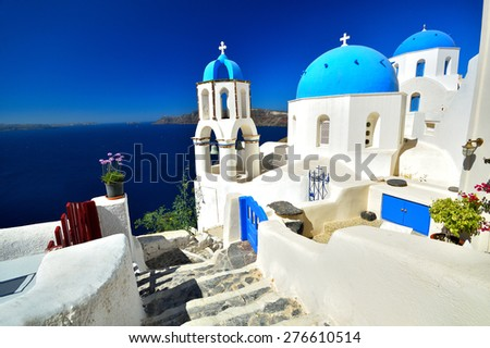 View of volcanic caldera and beautiful village of Oia with its whitewashed blue domed churches of Ag. Spyridonas and Ag. Anastasis, Oia, Santorini, Greece, Europe - stock photo