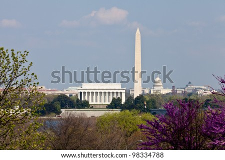 View of Washington DC skyline in late afternoon on a sunny day with Lincoln Memorial, Washington Monument and the Capitol with a blooming redbud - stock photo