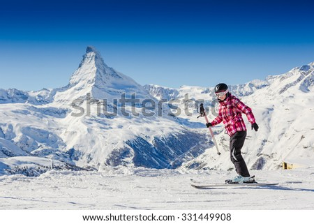 View of woman in mask standing during sunny winter day on Zermatt ski resort. Swiss Alps.  - stock photo