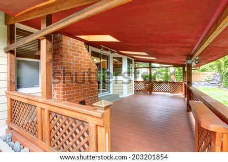 View of wooden backyard covered deck with railings - stock photo