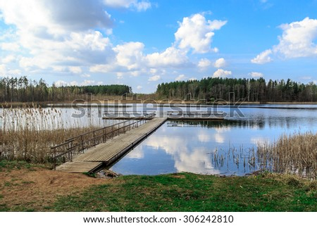 View of wooden pier inside lake, scenic view of reflection of the clouds and trees on lake, with cloudy blue sky background. - stock photo
