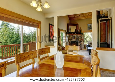View of wooden table set in the dining room with marble tile floor. The room is connected with living room and stone trim fireplace in the background