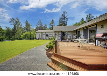 View of wooden walkout deck with patio area. Backyard garden with concrete walkway and green lawn.